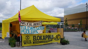 """En bild på elokapinas tält vid medborgarplatsen med skyltar som hänger med texten """"nälkälakko tulevaisuuden puolesta"""" swe: """"hungerstrejk för framtiden"""""""