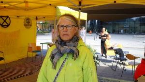 Eeva Kaila i en ljusgrön rock och halsduk inne i ett gult tält. Hon har glasögon på sig.