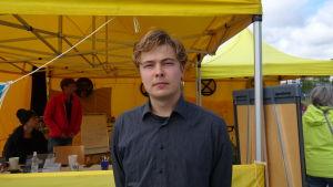 Amos Wallgren står utanför ett gult tält på medborgarplatsen i Helsingfors. Han tittar rakt in i kameran och är klädd en mörkblå kragskjorta.