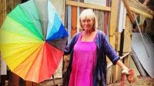 Antonia Ringbom, en äldre kvinna står på inspelningsplatsen med ett färggrannt paraply i handen.