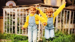 Två likadant klädda flickor hoppar upp i luften ute i en somrig trädgård