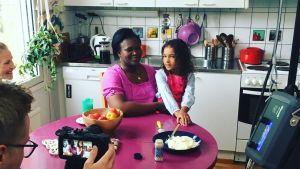En kameraman filmar en mamma och ett barn i ett kök