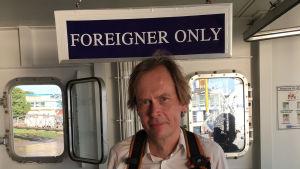 MAn på båt i bakgrunden skylt -foreigner only