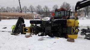 Plogbil ligger över spår och ett annat fordon försöker lyfta upp den. Myckey snö på marken.