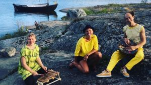 Tre musiker sitter på en klippa i skärgården och i bakgrunden syns en snipa