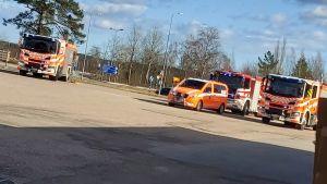 Flera räddningsfordon på en asfalterad plan.