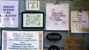 En vägg fylld med korsstygnstavlor med moderna citat