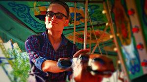Axel Åhman, medlem i humorgruppen KAJ och en av Vegas sommarpratare 2014 rider på en kamel i en karusell. Det är sommar