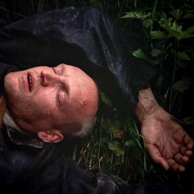 Stalker makaa silmät kiinni ruohikolla. Kuva elokuvasta Stalker (1979).