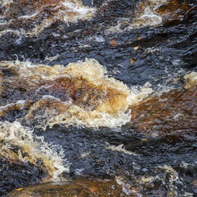 Virtaava rusehtava vesi.
