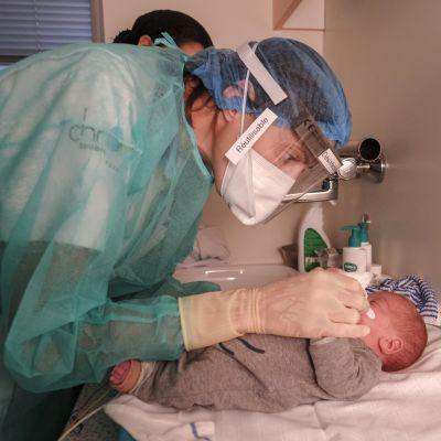 Sairaanhoitaja huolehti kolme kuukautta vanhasta vauvasta, jonka äiti (taustalla) näki lapsensa ensimmäistä kertaa.