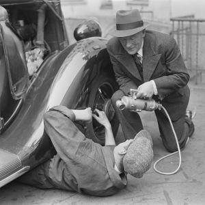 Yleisradion reportteri Alexis af Enehjelm haastattelemassa miestä, joka korjaa henkilöautoa auton alla 1930-luvulla.