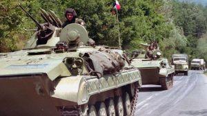 En konvoj militärfordon från Jugoslavien på en landsväg.