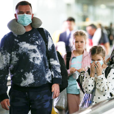 En familj med munskydd på en flygplats.