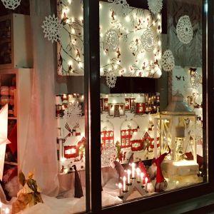 näyteikkuna, jossa jouluvaloja ja -tekstiilejä.