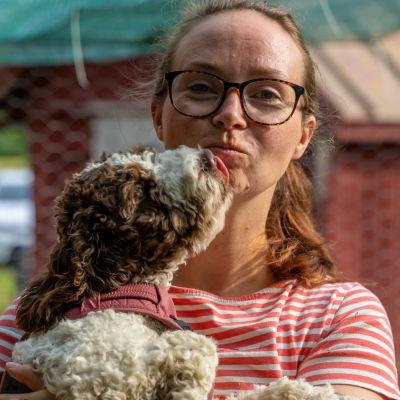 en kvinna står med en hundvalp i famnen.