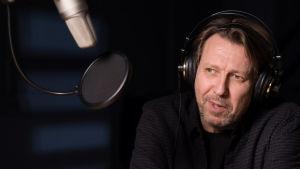 Martti Suosalon näyttelemä Jami juontaa radiolähetystä. Kuvassa mies ja mikrofoni.
