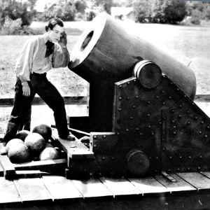 Buster Keaton seisoo valtavan mörssärin suulla ja kuulostelee, kuuluuko putkesta jotain. Kuva elokuvasta Kenraali.