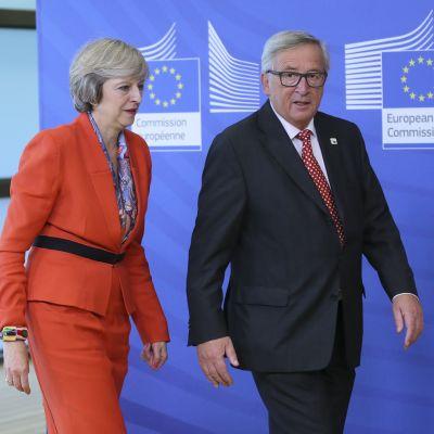 May ja Juncker kävelevät rinnakkain. Taustalla näkyy EU.n komission tunnuksin varustettu sininen seinä. Oikealla sivulla on Britannian lippu.