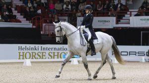 Dressyrryttaren Jenni Rintala sitter iförd dressyrdräkt på sin häst Nk Unique. Fotot är taget i manegen under tävling på Helsinki International Horse Show 2016.