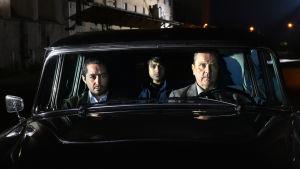 Khaled (Sherwan Haji) Mazdak (Simon Al-Bazoon) och Wikström (Sakari Kuosmanen) sitter i en gammal bil och tittar rakt fram.