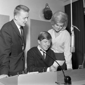 Hannu Kangaspunta, Markku Veijalainen ja Kaarina Leskinen tutkivat Veijalaisen kuuntelijan lähettämää korttia.