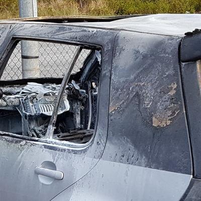 En del av en bränd grå personbil.
