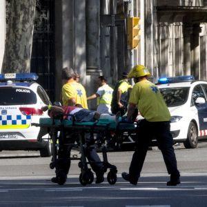 Räddningsmanskap bär på en bår med en skadad man efter att en bil körde in i folkmassa i Barcelona.