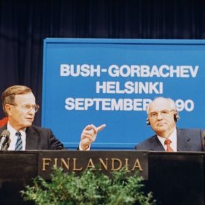 George Bush and Mikhail Gorbachev talking at a podium. In the background a poster stating Bush-Gorbachev Helsinki September 1990.