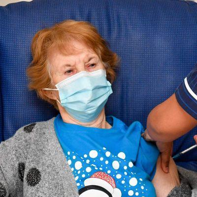En kvinna sitter i en stol och vaccineras av en sjukskötare.