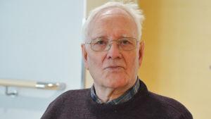 Närbild på en äldre man som tittar in i kameran. Bakom honom syns en vit vägg och en träfärgad dörr.