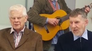 Två män sitter vid ett bord. I bakgrunden en man som spelar gitarr.