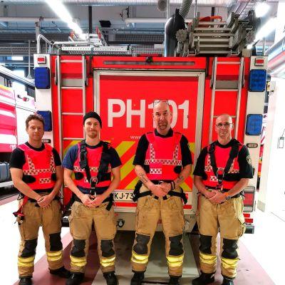 Päijät-Hämeen pelastuslaitoksen palomiehiä suojaliiveissä paloauton edessä.
