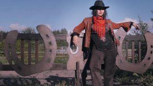 Stillbild av videoverk. Cowgirl-kvinna lutar mot staket.