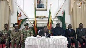 Robert Mugabe håller tal omgiven av militärens representanter.