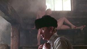 Harry Palmer (Michael Caine) hikoilee saunassa karvalakki päässä ja vaatteet yllä. Taustalla lauteilla alastomina Anya (Françoise Dorléac) ja Leo (Karl Malden).