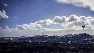 Vindkraftmöllor vid berg som är snötäckta. I bakgrunden kan man se blå himmel och vita moln.