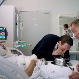 Tre män kring en patient som ligger medvetslös i en sjukhussäng. Den ena sniffar kokain.