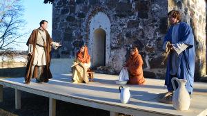 Fyra Fyra personer klädda i långa kåpor och kvinnorna i huvuddukar står på en scen uppbyggd framför Sibbo gamla kyrka. klädda i långa kåpor och kvinnorna i huvuddukar står på en scen uppbyggd framför Sibbo gamla kyrka.