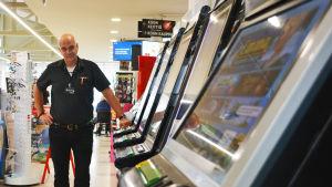 En man står bredvid en rad med spelautomater.