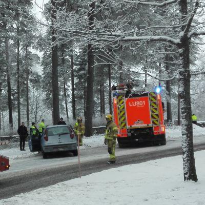 En bärgningsbil och en brandbil står vid en bil som varit med i en krock. Det är snö på marken.