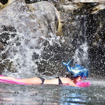 Nainen makaa kumipatjalla vedessä.
