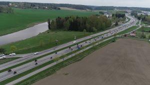 Luftfoto av hundratals motorcyklister som kör längs en riksväg förbi åkrar och en älv.