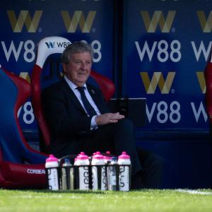 Ron Hodgson sitter ensam på en tom avbytarbänk iklädd kostym.