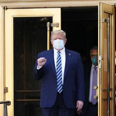 Donald Trump tervehtii poistuessaan Walter Reed Medical Centeristä 5. lokakuuta