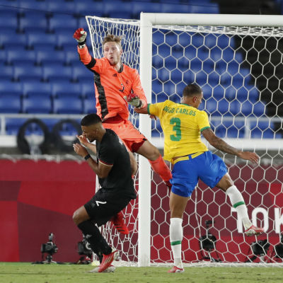 Målvakten Florian Müller i orange tröja rensar bort bollen i närkamp med en brasiliansk spelare med en tysk back i närheten..