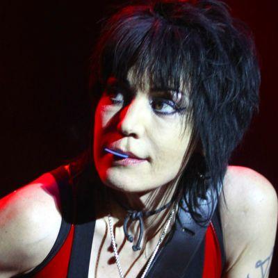 Joan Jett har ett plektrum i munnen.