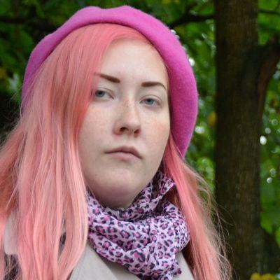 en kvinna i rosa hår och grå jacka står bland grönskande träd
