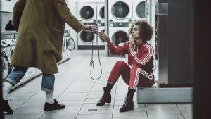 Nainen istuu pesulassa, mies ojentaa kännykkää.