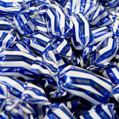 En hög med chokladtryffel med blåvitt omslagspapper.